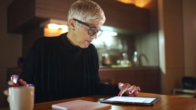 mogen kvinna som använder dator - jobba över bildbanksvideor och videomaterial från bakom kulisserna