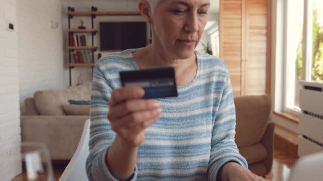 Mature woman using credit card and laptop for online banking at home.