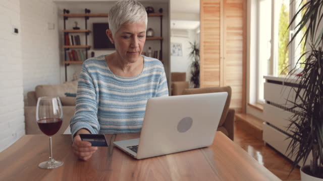 Mature woman using credit card and laptop for shopping on the internet.