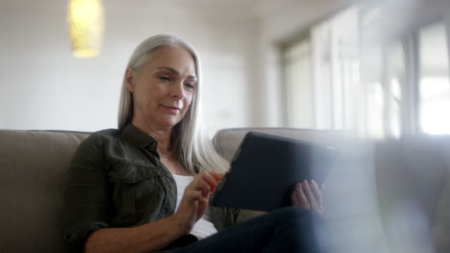 mature woman using digital tablet at home - 50 54 years stock videos & royalty-free footage