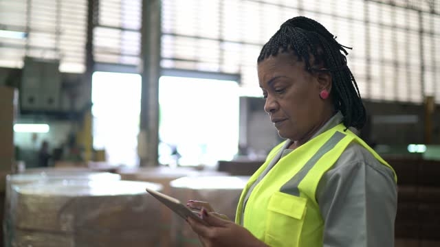 vídeos de stock e filmes b-roll de mature woman using digital tablet in a distribution warehouse - afro