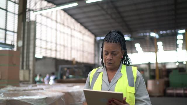 reife frau mit digitalen tablet s in einem distributionslager - distribution warehouse stock-videos und b-roll-filmmaterial