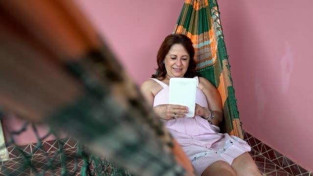 vídeos de stock, filmes e b-roll de mulher madura usando tablet digital em rede - rede de dormir