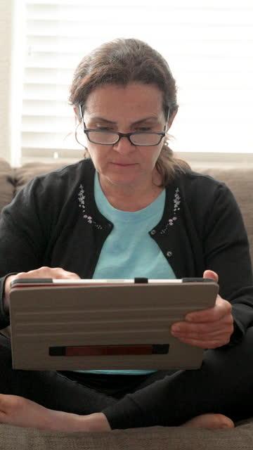 vídeos de stock, filmes e b-roll de mulher madura usando seu tablet digital sentado em seu sofá sala de estar - mulheres maduras