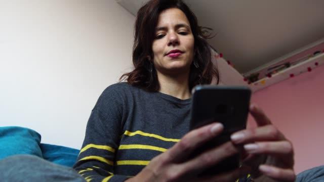 vídeos de stock, filmes e b-roll de maduras mulher usando seu smartphone sentado no sofá em casa - retrato - latino americano