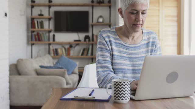 mature woman using laptop and taking notes on the paper. - to do list stock videos & royalty-free footage