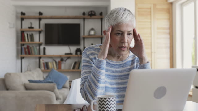 mature woman using laptop at home and feeling frustrated about an e-mail she has received. - only mature women stock videos & royalty-free footage