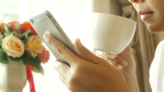 Reife Frau mit Telefon im Wohnzimmer und trinken heißen Tee