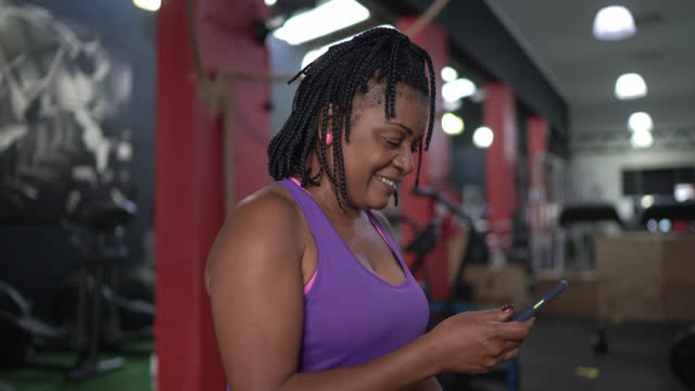 mature woman using smartphone at the gym - 50 54 years stock videos & royalty-free footage