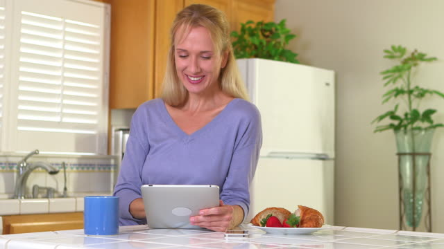 Mature woman using tablet and drinking coffee