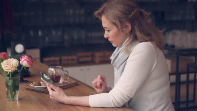 vídeos y material grabado en eventos de stock de mujer madura usando tableta mientras bebe té en café - cariñoso