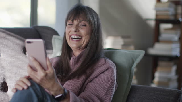 cu mature woman video chatting on her phone at home - senior women stock videos & royalty-free footage