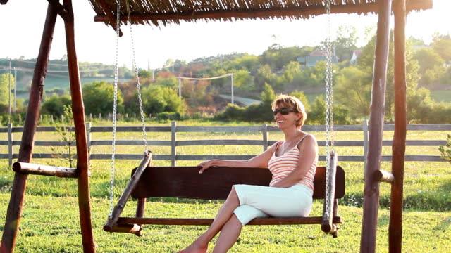 stockvideo's en b-roll-footage met mature woman - schommelen schommelstoel