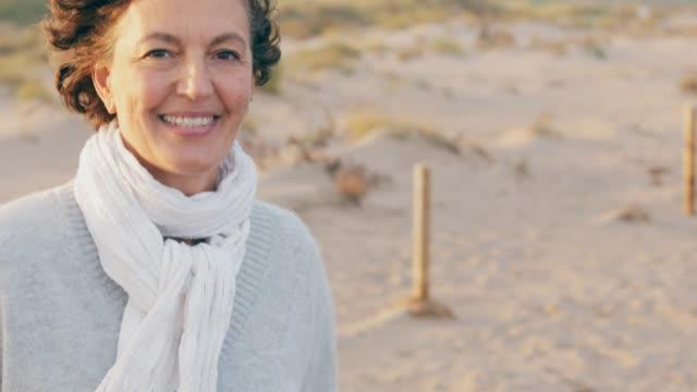 vídeos de stock e filmes b-roll de mature woman walking by the seaside at sunset. - 50 54 anos