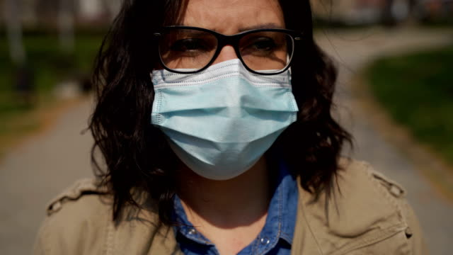mature woman walking through park  with protective mask in corona virus pandemic - mental health stock videos & royalty-free footage