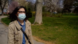 Mature woman walking through park  with protective mask in corona virus pandemic