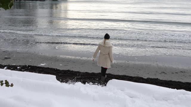 reife frau geht im winter am strand entlang - wintermantel stock-videos und b-roll-filmmaterial