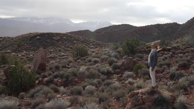 mature woman walks along desert track, into mountains - moab utah stock videos & royalty-free footage