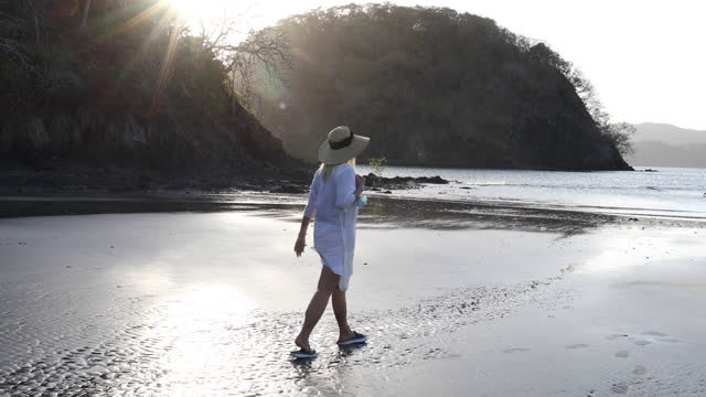 mature woman walks along empty beach, at sunrise - protection stock videos & royalty-free footage