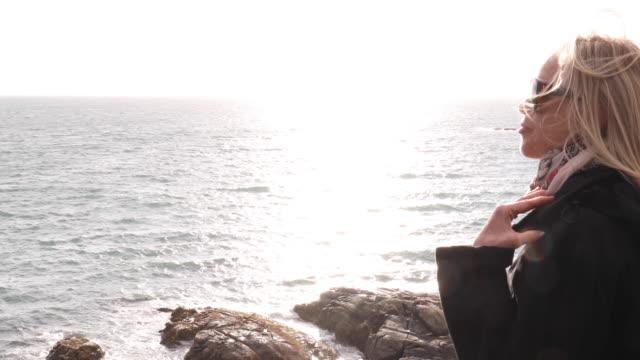 mature woman walks along windy headland above ocean - the way forward stock videos & royalty-free footage