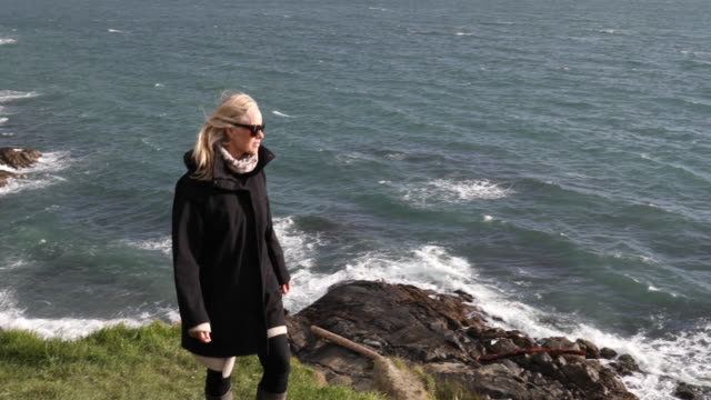 mature woman walks along windy headland above ocean - travel destinations stock videos & royalty-free footage