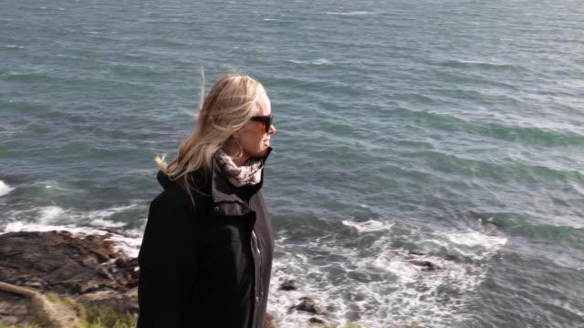 mature woman walks along windy headland above ocean - cape stock videos & royalty-free footage