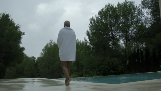 mature woman walks in the rain - wrapped in a towel stock videos & royalty-free footage