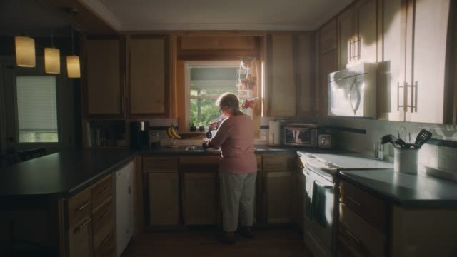 vídeos de stock e filmes b-roll de mature woman walks into home kitchen and pours a cup of coffee in the morning light. - casa