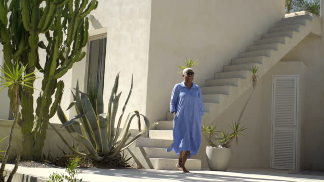 vidéos et rushes de mature woman walks through luxury villa - 60 64 ans