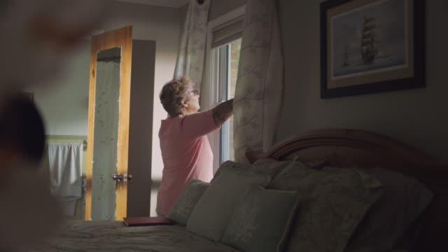 slo mo. mature woman walks to bedroom window and pulls open the curtains to look outside in the morning light. - abgeschiedenheit stock-videos und b-roll-filmmaterial