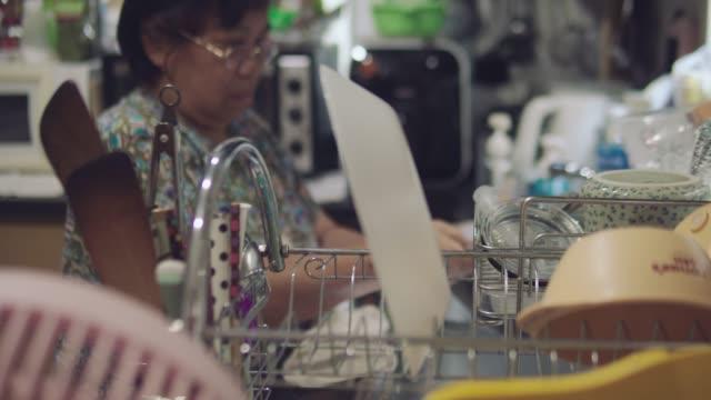 vídeos de stock e filmes b-roll de mature woman washing dish and putting on dish racks - feito pelo homem