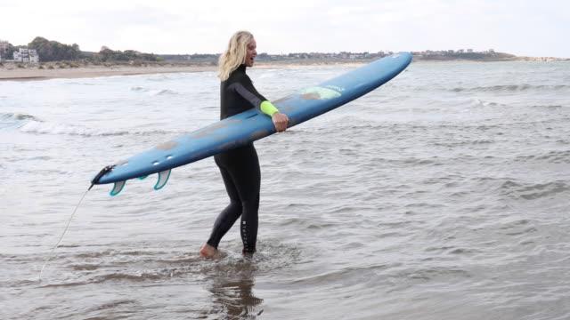 vidéos et rushes de la femme mûre regarde surfer, planche de fixation - commencement