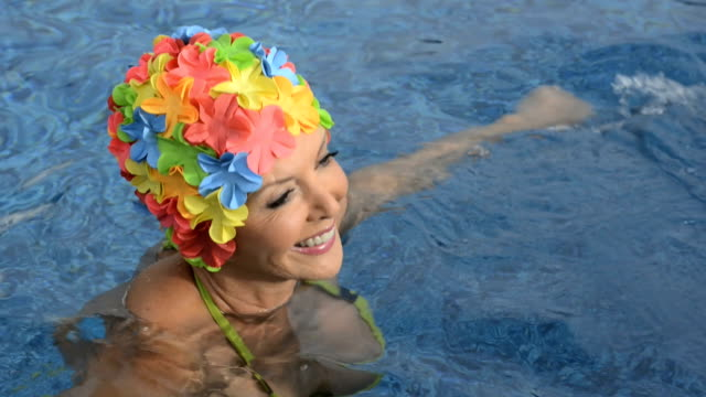 mature woman wearing a floral swimming cap - swimming cap stock videos and b-roll footage