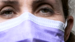 Mature woman wearing a medical mask looking at the camera