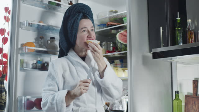 mature woman wearing bathrobe and towel turban is eating a cream cheese toast next to the fridge - wearing a towel stock videos & royalty-free footage