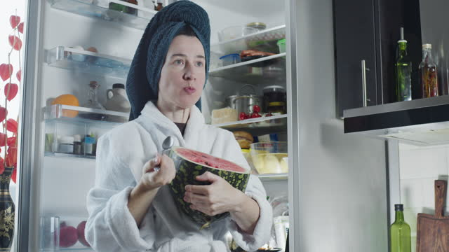 mature woman wearing bathrobe and towel turban is eating a half of watermelon next to the fridge - wearing a towel stock videos & royalty-free footage