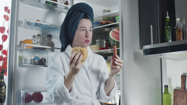 mature woman wearing bathrobe and towel turban is eating a sausage and a sandwich next to the fridge - wearing a towel stock videos & royalty-free footage