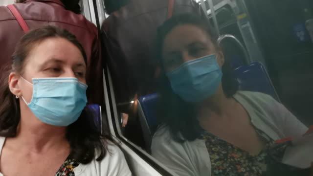 vidéos et rushes de femme mûre utilisant le masque de visage pour la protection au métro - confinement