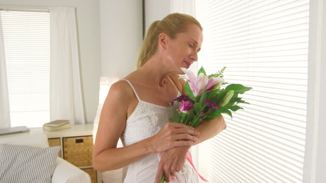 Mature woman with bouquet of flowers standing by window