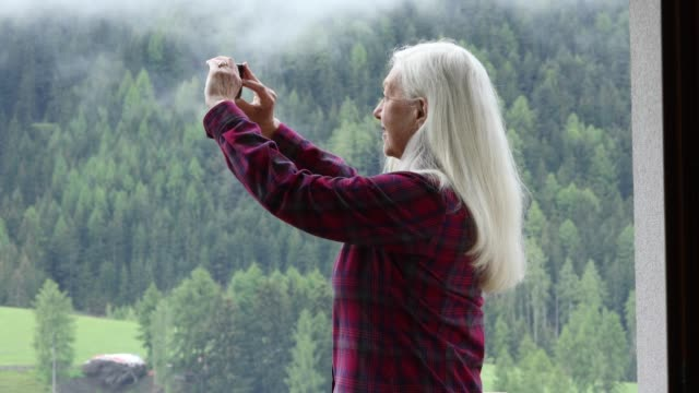vidéos et rushes de mature woman with camera by forest in san pietro, italy - cheveux gris femme