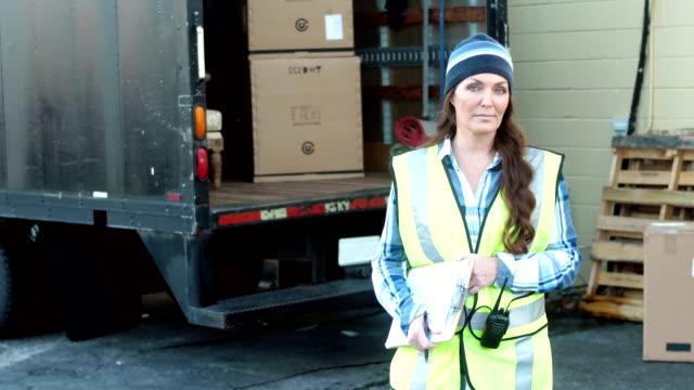 mature woman with delivery truck writing on clipboard - manual worker stock videos & royalty-free footage