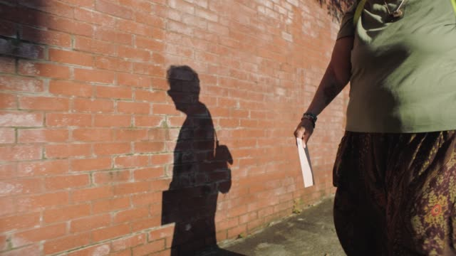 slo mo. mature woman with envelope to mail walks down neighborhood sidewalk as her shadow walks beside her cast against a brick wall. - high street stock videos & royalty-free footage