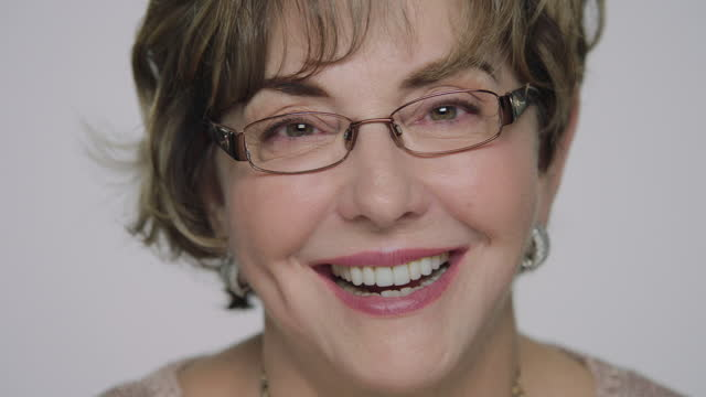 CU SLO MO. Mature woman with glasses laughs and smiles at camera in white studio.