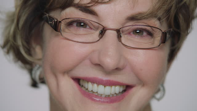 CU SLO MO. Mature woman with glasses opens her eyes and smiles at camera in slow motion.