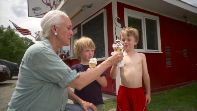 MS Mature woman with grand children (4-7) eating ice cream cone / Stowe, Vermont, USA