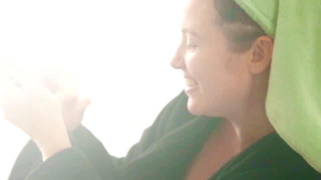 Reife Frau mit Haar Handtuch mit Mobiltelefon und Getränke