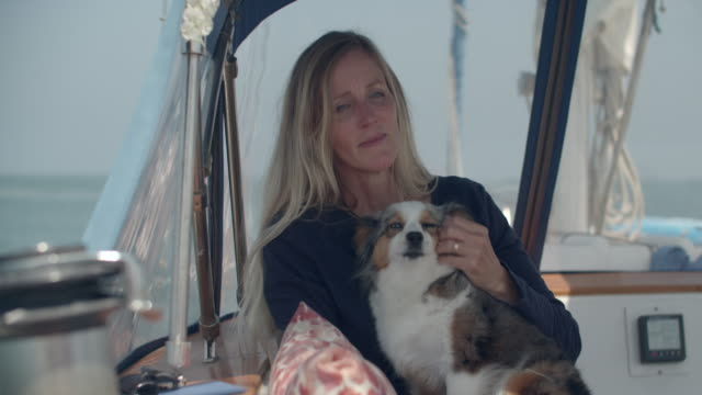 stockvideo's en b-roll-footage met mature woman with her dog on a sailboat - australische herder