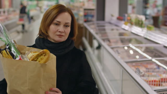 Mature woman with paper bag full of groceries
