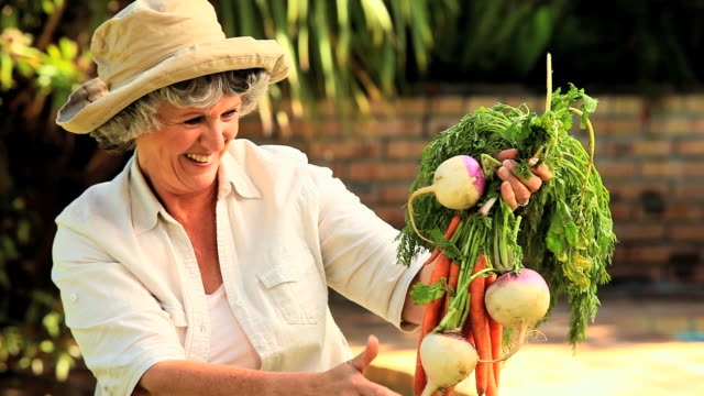 stockvideo's en b-roll-footage met mature woman with root vegetables / cape town, western cape, south africa - alleen één oudere vrouw