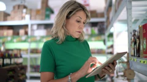 reife frau arbeiter zu fuß und mit tablet im großhandel - drehort außerhalb der usa stock-videos und b-roll-filmmaterial